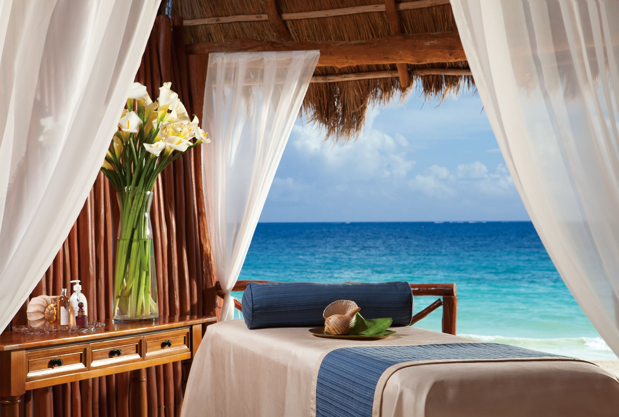 Oceanfront treatment room of a spa with a massage bed