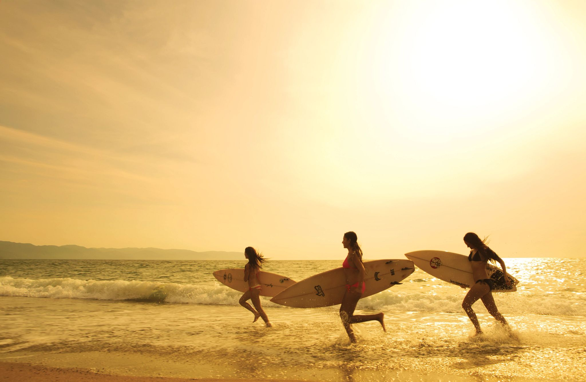 three women running on the beach with their surfboards