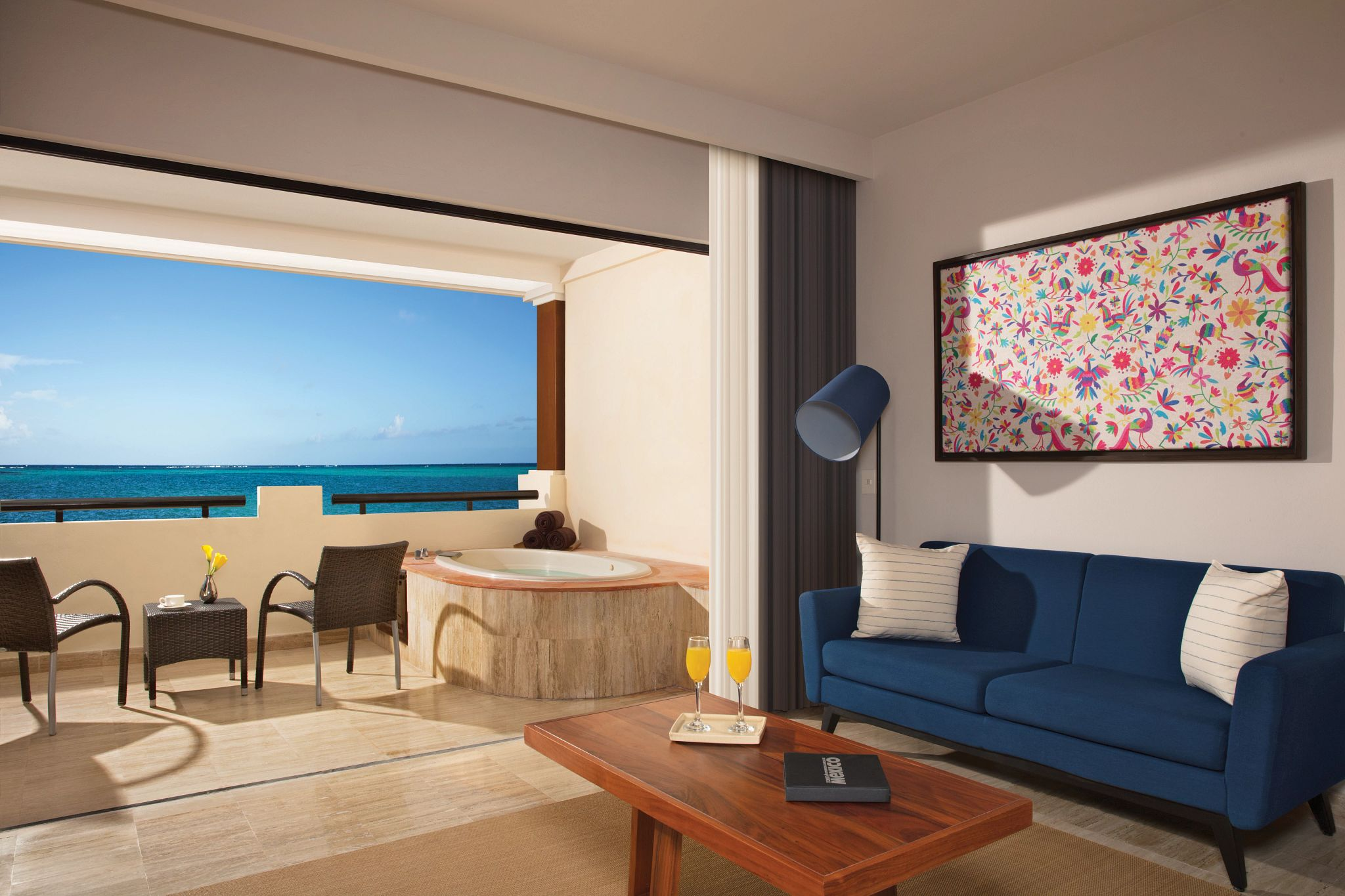 living area and terrace of a hotel suite with an ocean view