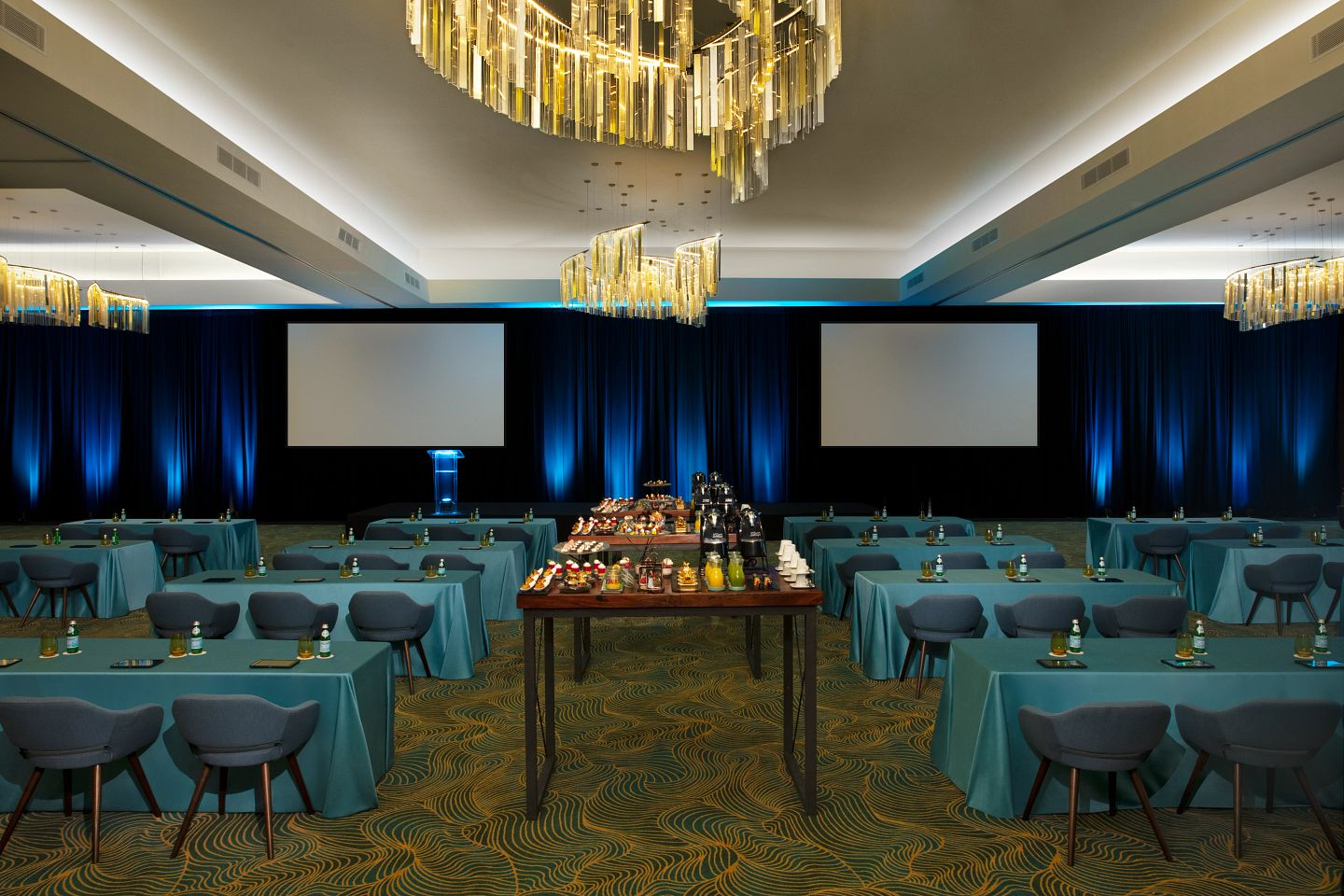 ballroom meeting set-up with ample seating, projectors and food