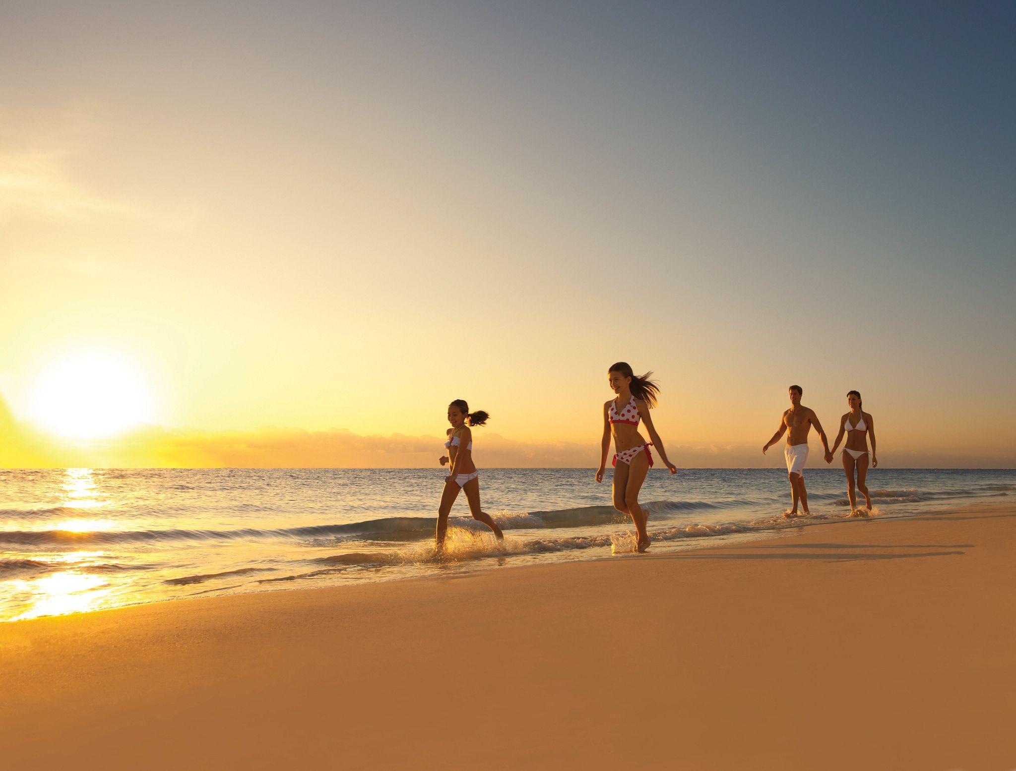 famliy walking along the beach at sunset