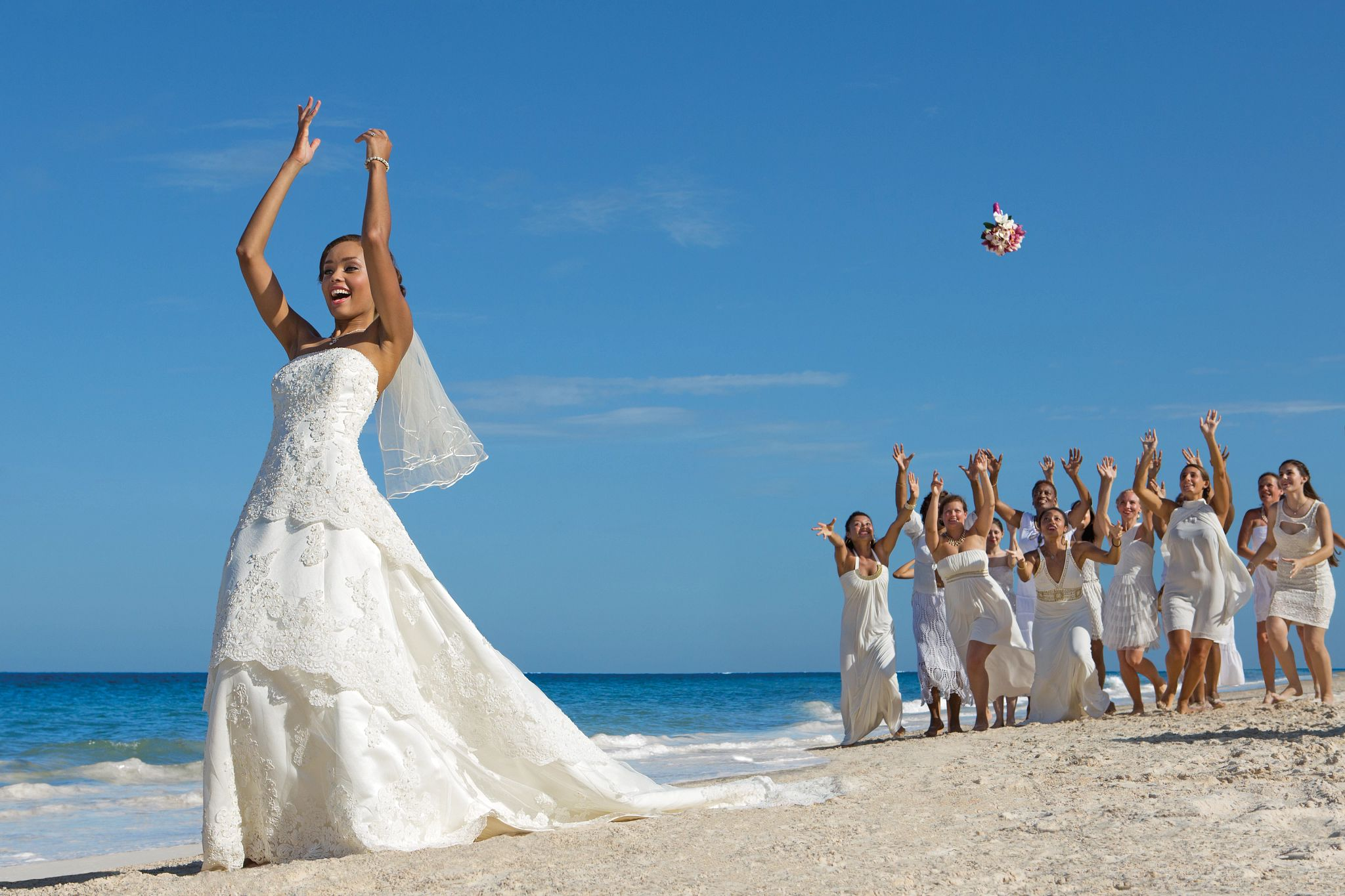 Bride tossing bouquet to group of women on the beach