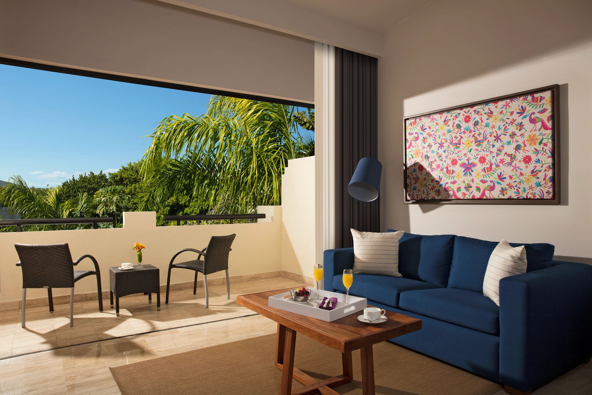 living area and terrace of a hotel suite with a tropical view