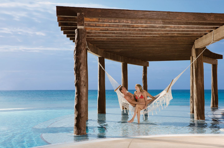 couple in hammock on beach under a dock