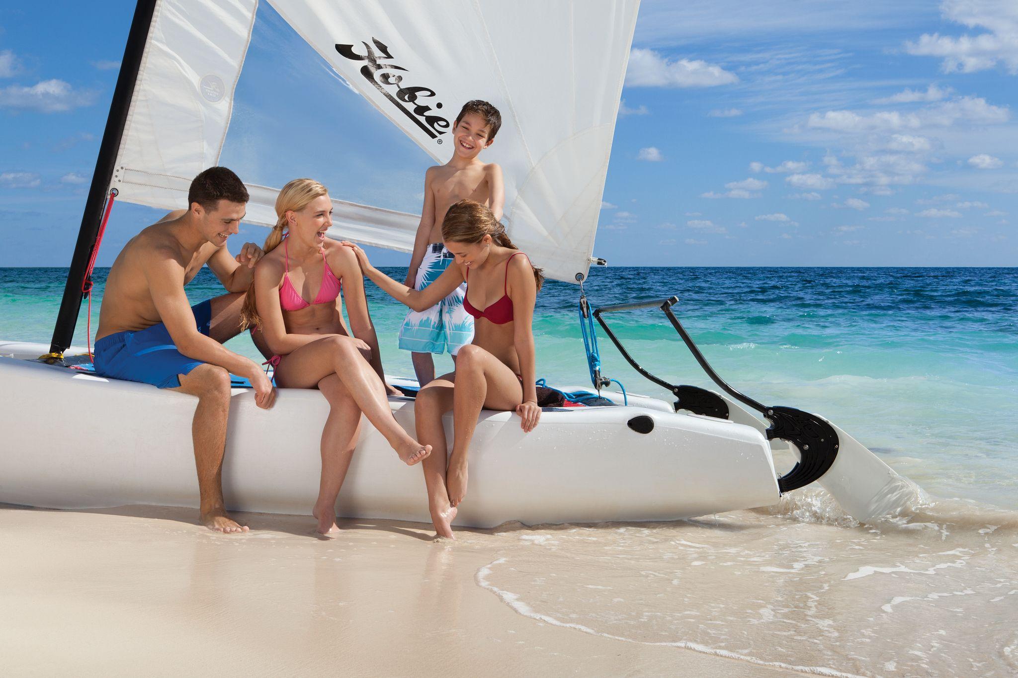 Family sitting on a catamaran on the beach
