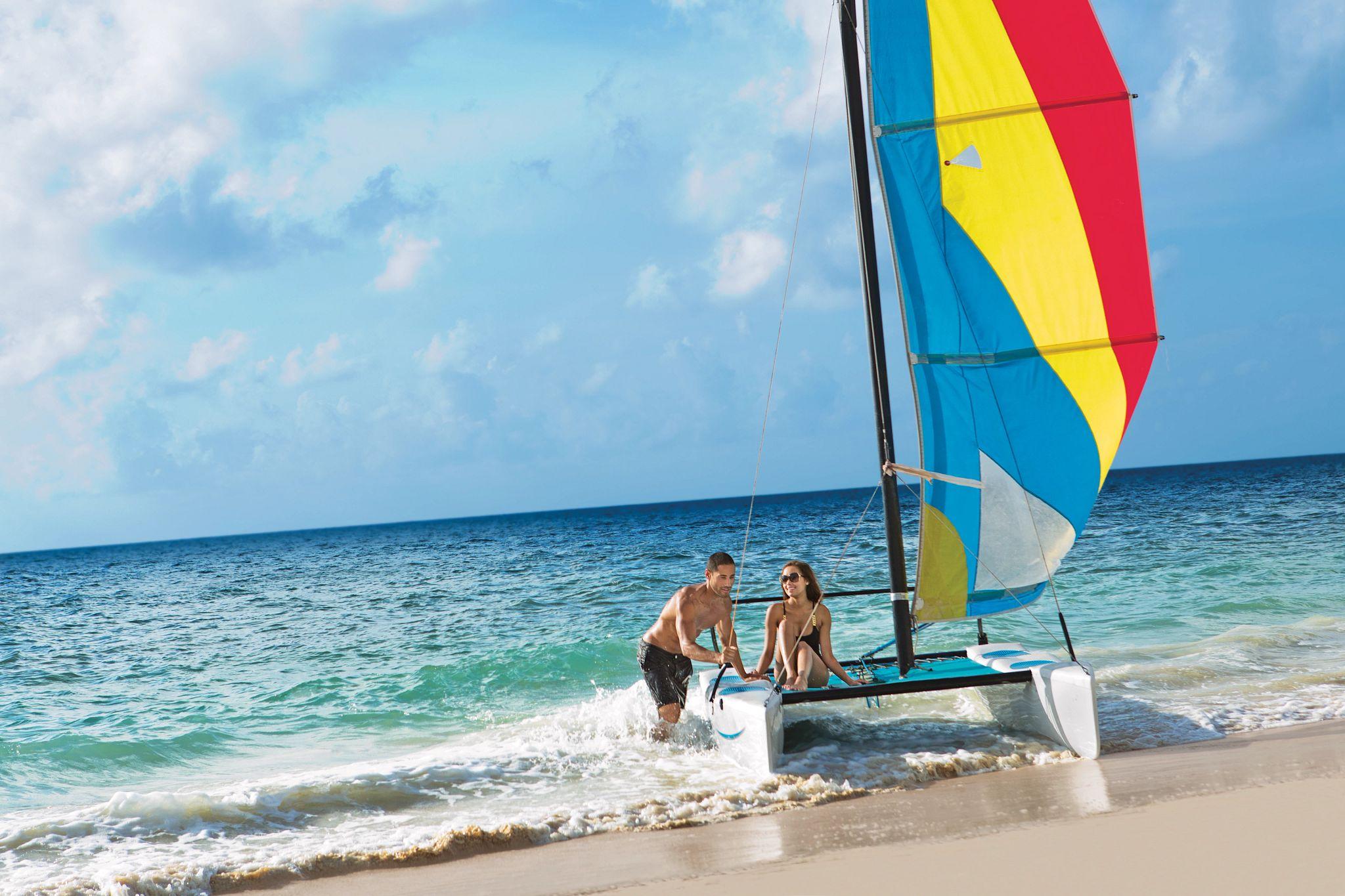 Couple sitting on a catamaran on the beach