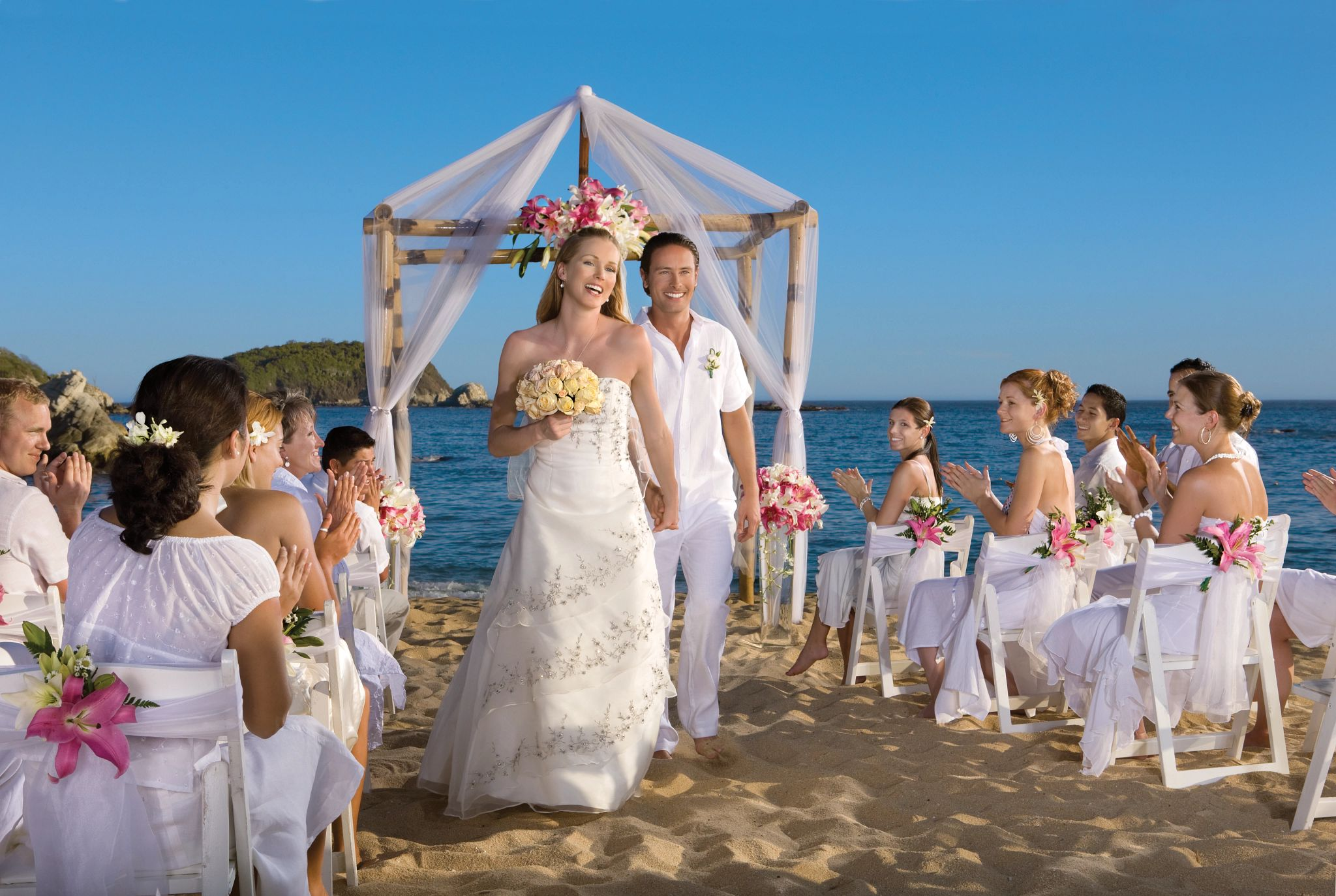 Newlywed Couple walking together past seated guests applauding them at the conclusion of the wedding ceremony on the beach